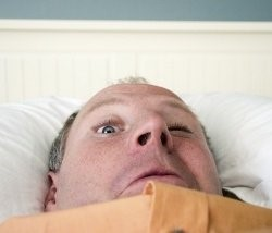man with one eye open in bed, humorous