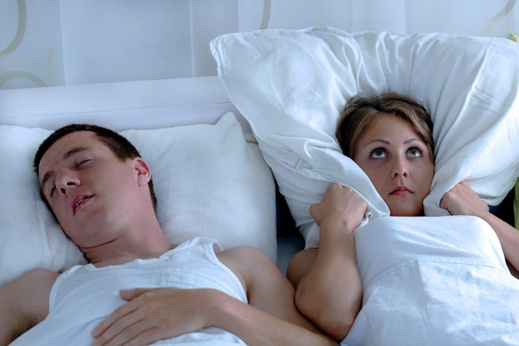 Young, irritated couple sleeping