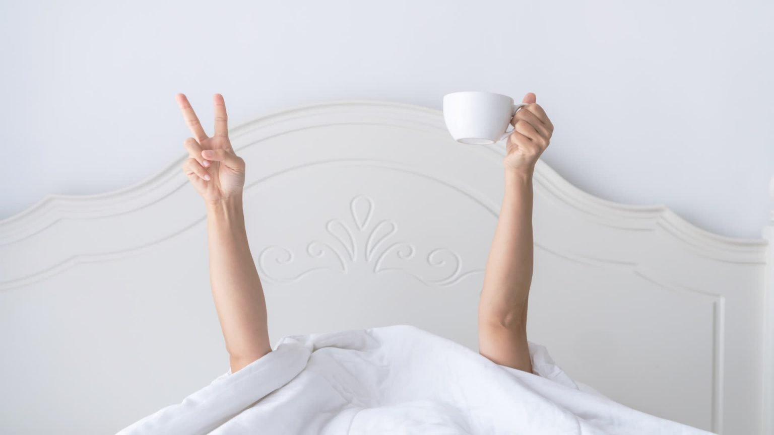woman in bed with peace sign and coffee